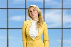 Successful young business lady. Smiling business woman standing on blue sky office window background Stock Photo