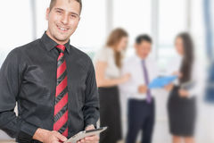 Successful young business man holding tablet pc and business team Royalty Free Stock Images