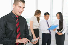 Successful young business man holding tablet pc and business team Royalty Free Stock Photo