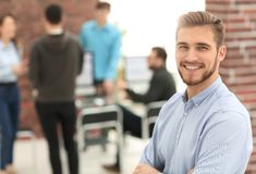 Successful young business man standing with his colleagues in b. Successful young businessman standing with colleagues on the background in the office stock photography