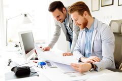 Successful business partners brainstorming in modern office. Successful young business partners brainstorming in office royalty free stock image