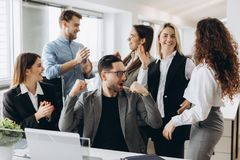 Successful young business people are raising hands in fists and screaming with happiness while working with a computer in business stock images