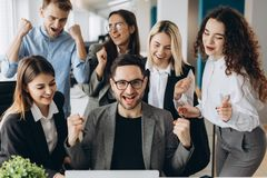 Successful young business people are raising hands in fists and screaming with happiness while working with a computer in business royalty free stock image