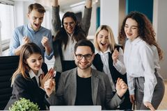 Successful young business people are raising hands in fists and screaming with happiness while working with a computer in business stock photography