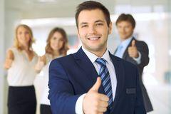 Successful young business people showing thumbs up sign while standing in office interier Stock Photo
