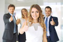 Successful young business people showing thumbs up sign Stock Photo