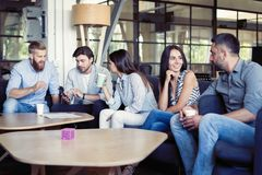Successful young business people are talking and smiling during the coffee break in office. Successful young business people are talking and smiling during the royalty free stock photo