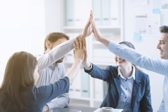 Successful young business team giving high five. While sitting around the desk, teamwork and cooperation concept stock photos