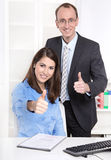 Successful young business team with thumps up - man and woman. Stock Photos