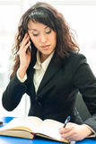 Successful business woman at office workplace with mobile cell phone Royalty Free Stock Images