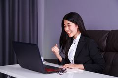 Successful business woman raising arm in happiness with laptop c Stock Photo