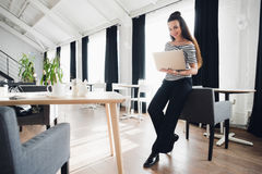 Successful young business woman is standing near table and chair while looking at the camera and holding a laptop. Successful young business woman is standing stock photo