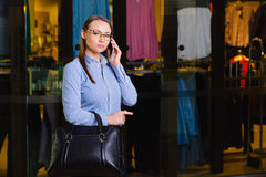 Successful Young Business woman talking on Mobile Phone,. Walking Inside the Mall. Behind her shop with clothes Stock Image