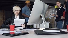 Successful young business woman working in modern office using computer touch screen, looking at monitor. Business team