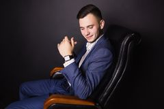 Successful young businessman in business suit. A successful young businessman in a business suit and white shirt and a fashionable watch on his arm on a black Stock Images