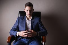 Successful young businessman in business suit. A successful young businessman with a confident look in a business suit and white shirt and a fashionable watch on Royalty Free Stock Photo