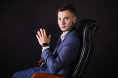 Successful young businessman in business suit. A successful young businessman in a business suit and white shirt and a fashionable watch on his arm on a black Royalty Free Stock Photos