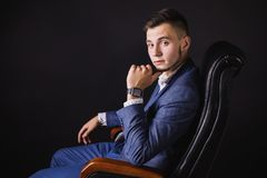 Successful young businessman in business suit. A successful young businessman in a business suit and white shirt and a fashionable watch on his arm on a black Stock Photos