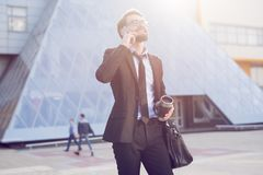 Successful and young businessman with coffee and smartphone in hands royalty free stock images