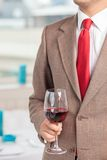 Successful young businessman is drinking alcohol. Close up of body of well-dressed man holding a wineglass. He is standing and tasting red wine Stock Images