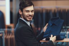 Successful young businessman in suit chooses shirt to buy. Boutique of business suits. New suit purchase Stock Images