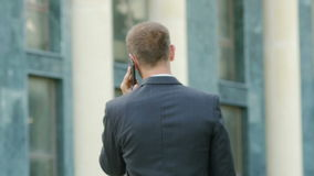 Successful young businessman talking on the phone walking near the administrative building. In slow motion stock footage