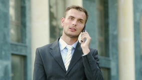 Successful young businessman talking on the phone walking near the administrative building. In slow motion stock video