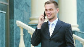 Successful young businessman talking on the phone walking near the administrative building. stock footage
