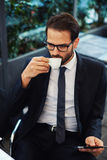 Successful young businessman waiting for a business partner. Portrait of smart attractive businessman in glasses drink coffee during his outdoors breakfast stock photography