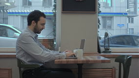 Successful young businessman is working on his laptop in cafe and drinking coffee stock footage