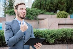 Successful young businessman working on a tablet in front of an office building. Holding hand on chin and looking into distance royalty free stock images