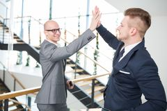 Businessmen Giving Highfive In Office royalty free stock image
