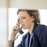 Successful young businesswoman sitting at her desk making a phone call royalty free stock photo