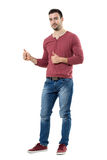 Successful young casual man showing thumbs up looking at camera. Full body length portrait isolated over white background Royalty Free Stock Image