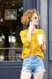 Successful young coffee shop owner. Portrait of a young woman standing in the doorway of her store while making call on her cellphone Royalty Free Stock Photo
