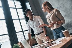 Successful and young. Confident business people talking while wo. Rking in the office royalty free stock photography