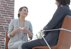 A relaxed conversation of a man and a woman in the office Stock Photos