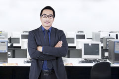Successful young employee standing in office Royalty Free Stock Image