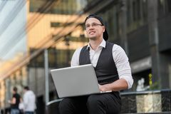 Successful freelancer working with laptop outdoors. Successful young freelancer working with laptop outdoors in front of office building Stock Images