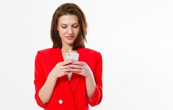Successful young girl in a classic red suit chats chatting with someone on a device isolated on white - Copy space, mock up. Business communication concept stock photo