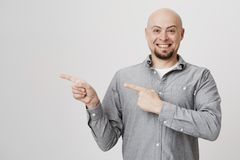 Successful young handsome man smiling happily while showing direction with his fingers over white background. Bearded Royalty Free Stock Photography