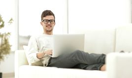 Successful young male freelancer working on laptop at home. Photo with copy space Stock Image