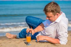 Successful young man resting by the sea Royalty Free Stock Image