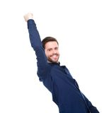 Successful young man smiling with arms raised. Portrait of a successful young man smiling with arms raised on isolated white background Royalty Free Stock Images