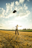 Successful Young Man Throwing his Coat in the Air. Successful Young Businessman in an Open Field, Throwing his Coat in the Air with Arms Wide Open Against Stock Image