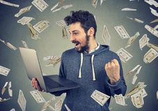 Successful young man using laptop building online business earning money. Successful young man using laptop building online business making money dollar bills royalty free stock photos