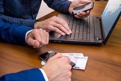 Successful young man using laptop for sale. concept making money. Euro bills Stock Image
