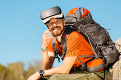 Successful young man, using virtual reality goggles to tour in mountains, on vacation in summer Royalty Free Stock Photos