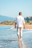 Successful young man walking along a  beach Royalty Free Stock Images