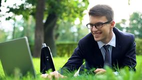 Successful young manager lying on green grass, smiling and chatting on laptop. Stock photo stock photos